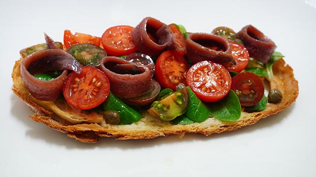 Tosta de anchoas en conserva con tomates